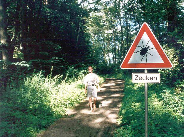 OD Spaziergänger im Wald mit Zeckenwarnschild